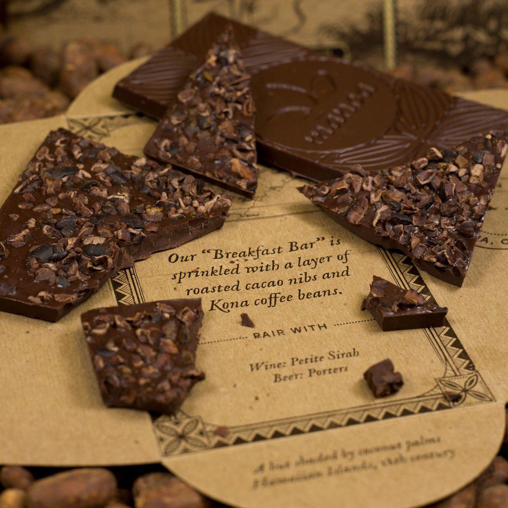 Geopende verpakking Manoa, breakfast bar, chocoladereep en gebroken stukken chocolade zichtbaar.