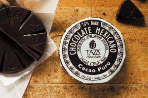 Taza chocolade ligt op houten tafel, een stuk in verpakking, een disk open op wikkel en los stukje.